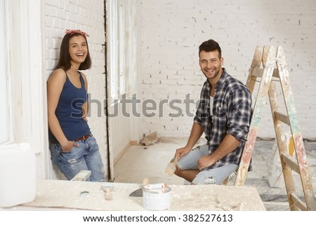 Happy couple renovating house, smiling, looking at camera.