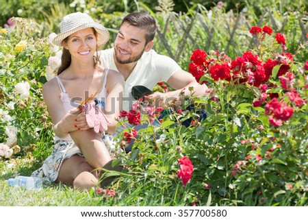 Happy couple resting at the flowers garden and smiling at summer vacation