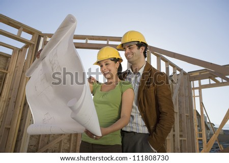 Happy couple reviewing blueprint at construction site - stock photo