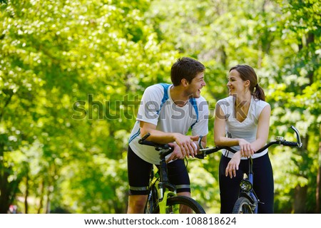 Happy couple riding bicycle outdoors, health lifestyle fun love romance concept - stock photo