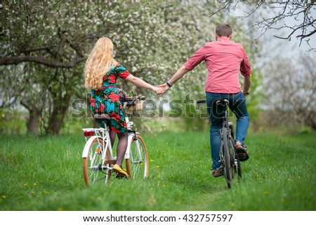 Happy couple riding bicycles in the spring garden back to camera and holding hands. Female with long blond hair wearing flowered dress and man in a red shirt
