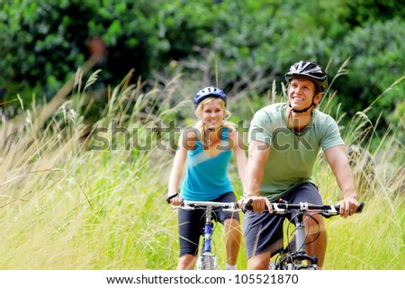 Happy couple riding bicycles outside, healthy lifestyle fun concept. mountain bike fitness outdoor exercise together - stock photo