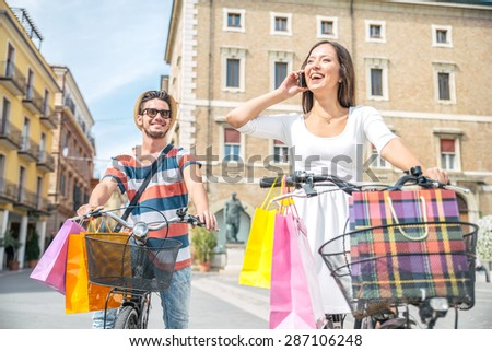 Happy couple riding bikes in the city - Young man and woman with shopping bags and she speaks at mobile phone - stock photo