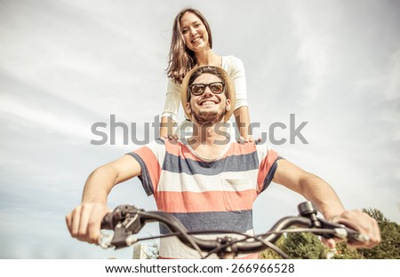happy couple riding together on one bicycle. concept about spring, couples, love, fun, happiness, nature and healthy lifestyle - stock photo