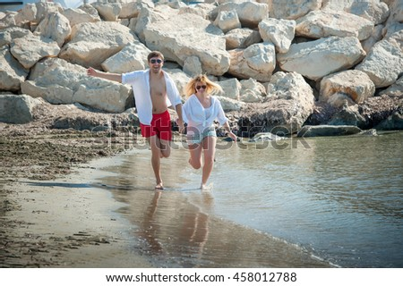 happy couple running along the beach near the rocks stones