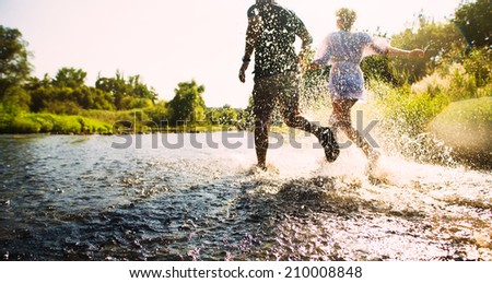 Happy couple running in shallow water. Summertime. - stock photo