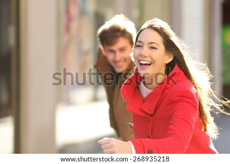 Happy couple running in the street in a sunny day - stock photo