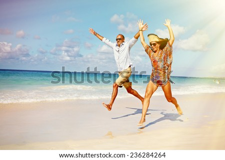 Happy couple running on the beach. Crazy vacation - stock photo