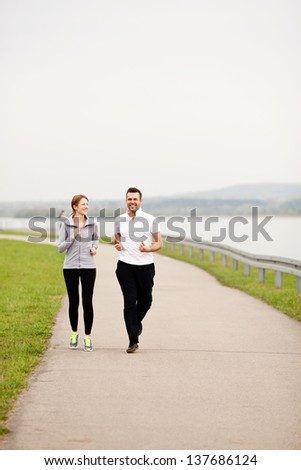 Happy couple running outdoors. - stock photo
