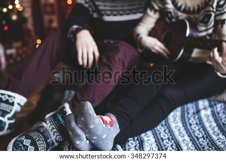 Happy couple's feet, playing guitar, Christmas time