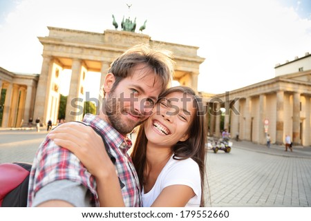Happy couple selfie selfportrait in front of Brandenburg Gate or Brandenburger Tor, Berlin, Germany. Beautiful young multiracial travel couple having fun on Europe vacation. Asian woman, Caucasian man - stock photo