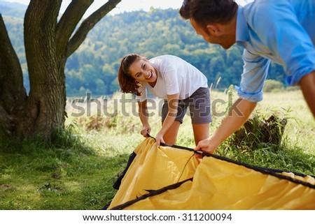 Happy couple setting up tent - stock photo