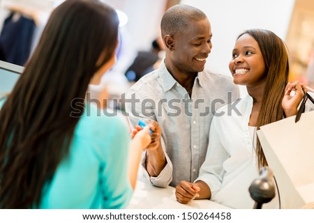 Happy couple shopping and making payment with a credit card  - stock photo