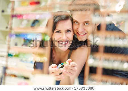 Happy couple shopping for bangle at jewelry store - stock photo