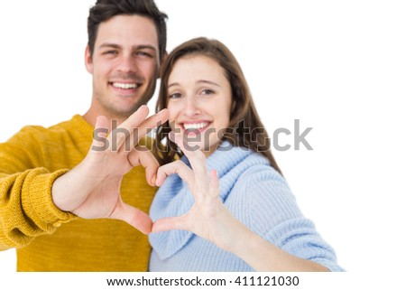 Happy couple showing a heart shape with their fingers on white background - stock photo