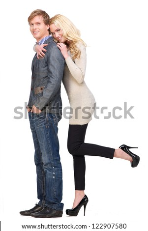 Happy couple showing happiness. Full length portrait isolated on white background. Casual male with hands in his pockets and beautiful blonde female leaning over his shoulder. - stock photo
