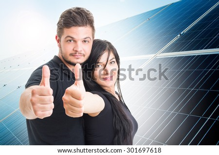 Happy couple showing like on solar power photovoltaic panel background  as green energy solution concept - stock photo