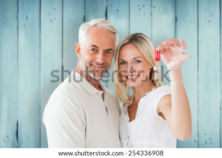 Happy couple showing their new house key against wooden planks - stock photo
