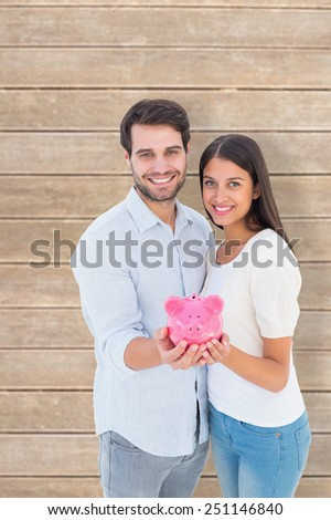 Happy couple showing their piggy bank against wooden planks - stock photo