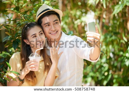 Happy couple showing wedding ring when photographing