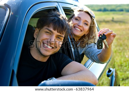 Happy couple showingh the keys sitting in new car