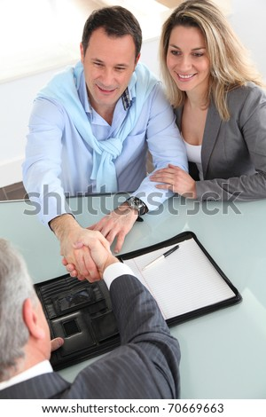 Happy couple signing purchase contract with real-estate-agent - stock photo