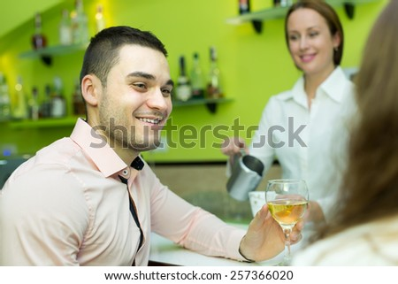 Happy couple sitting at bar and female bartender pouring coffee. Focus on man - stock photo