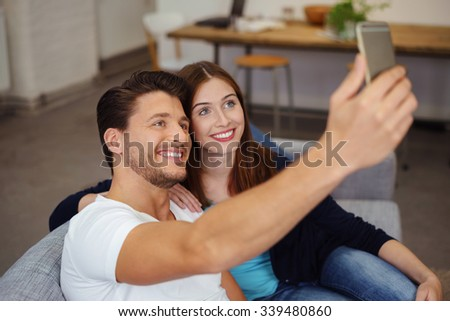Happy couple sitting close together on a comfortable sofa in the living room smiling and posing for a selfie on their smartphone - stock photo