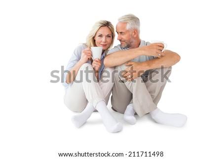 Happy couple sitting holding mugs on white background - stock photo