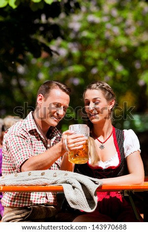 Happy Couple sitting in Bavarian Beer garden and enjoy the beer and the sun - stock photo
