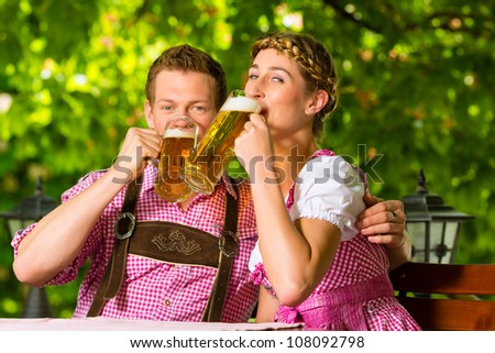 Happy Couple sitting in Beer garden in summer and enjoy a glass of beer and the sun