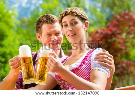 Happy Couple sitting in Beer garden in summer and enjoying a glass of beer and the sun - stock photo