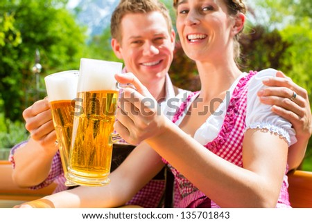 Happy Couple sitting in Beer garden in summer and enjoying a glass of beer and the sun