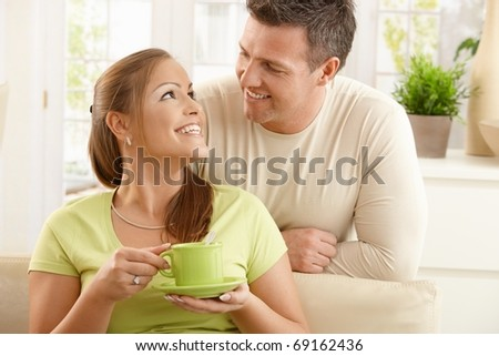 Happy couple sitting in living room, woman holding tea cup with two hands looking up at man smiling.?