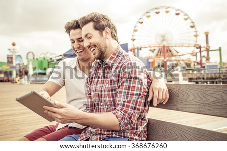 Happy couple sitting in Santa Monica pier. Young men watching something on a digital tablet. Concept about technology and relationship - stock photo