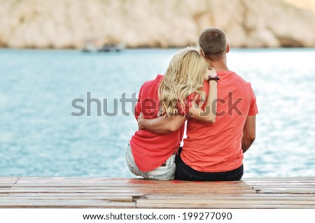 Happy couple sitting in summer near lake during sunset - stock photo