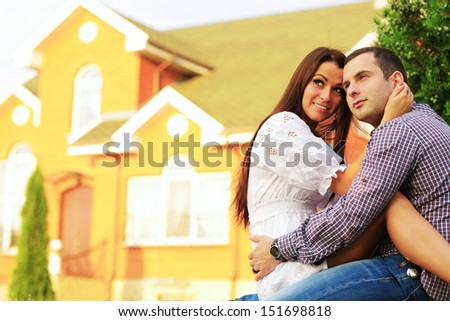 Happy couple sitting in the garden in front of new home - stock photo