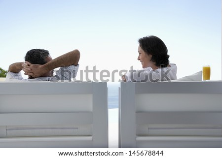 Happy couple sitting on armchairs enjoying vacation in resort