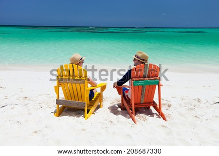 Happy couple sitting on colorful adirondack chairs at tropical beach enjoying Caribbean vacation  - stock photo