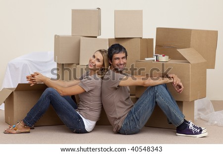 Happy couple sitting on floor around boxes after buying house - stock photo