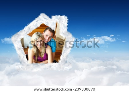 Happy couple sitting on floor handing a glass of champagne against bright blue sky over clouds - stock photo