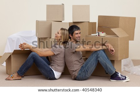 Happy couple sitting on floor unpacking boxes after moving house