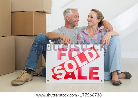 Happy couple sitting on floor with sold sign in their new home - stock photo