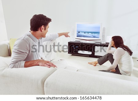 happy couple sitting on sofa and watching television together  - stock photo