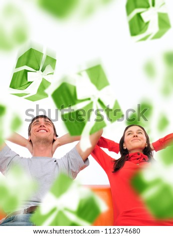 Happy couple sitting on sofa at home and dreaming about something. Gift boxes are falling down on them - stock photo
