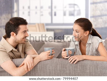 Happy couple sitting on sofa at home, drinking tea, smiling at each other.? - stock photo