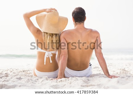 Happy couple sitting on the beach on a sunny day - stock photo