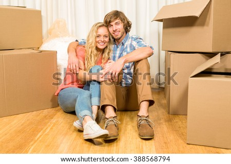 Happy couple sitting on the floor in new home - stock photo