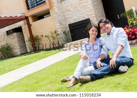 Happy couple sitting outdoors in the front yard - stock photo