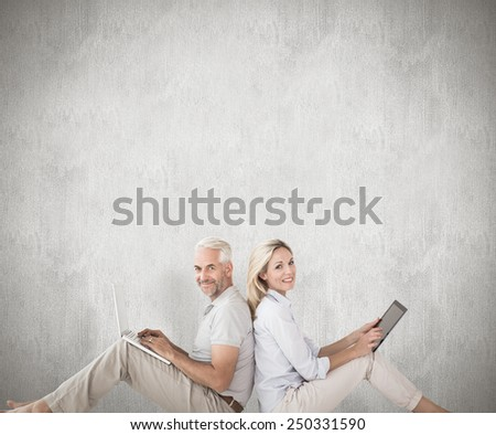 Happy couple sitting using laptop and tablet pc against weathered surface - stock photo